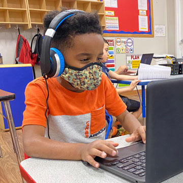 boy on computer with mask