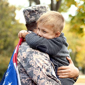 kid hugging his dad in uniform
